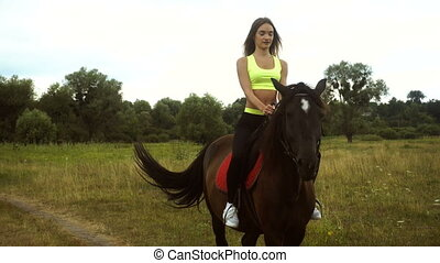 lovely girl riding astride beautiful Brown horse outdoors