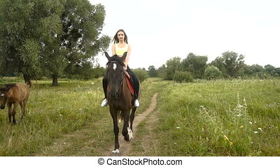 cute girl riding astride beautiful Brown horse outdoors