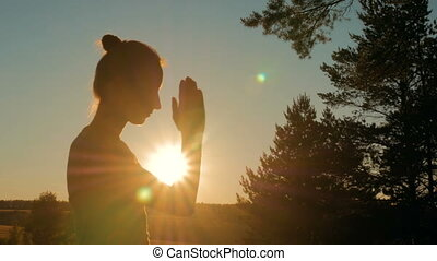 Sporty woman praying in forest at sunset - Silhouette of...