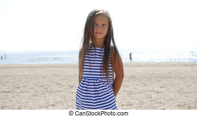 girl in striped dress standing on the beach and squints eyes