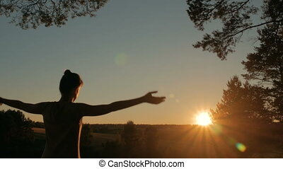 Woman practicing yoga in forest at sunset - Woman practicing...