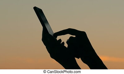 Woman using smartphone in forest after sunset. Relax, nature...