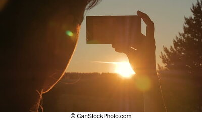 Woman silhouette taking photo of sunset with smartphone