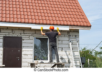 builder works on the roof - builder makes the eaves of the...