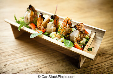 Grilled tiger shrimp served with parsley on a wooden board