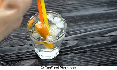 Cocktail with ice on dark wooden table - Hand stirs with...