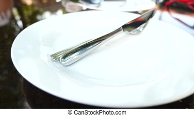 Empty white plate and cutlery on it. fork and knife. slow...