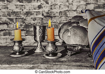 Silver kiddush cup, crystal candlesticks with lit candles,...