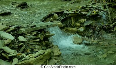 Water from a mountain stream cascades over large boulders.