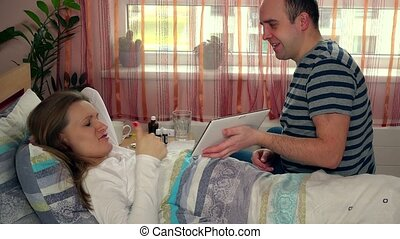man husband with tablet computer entertain his sick wife woman in bed
