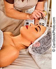 Woman massage beauty salon. Electric stimulation female skin...
