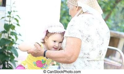 Grandmother and granddaughter play and hug
