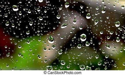 Drops of rain on a window glass on a green background