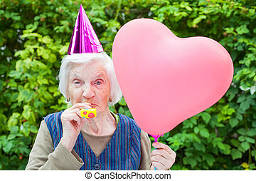 Elderly woman celebrating birthday - Picture of a happy...