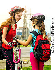 Bicycle tire pumping by child bicyclist. Girl repair bicycle on road.