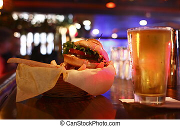 Glass of beer and burger in a dimly lit bar.