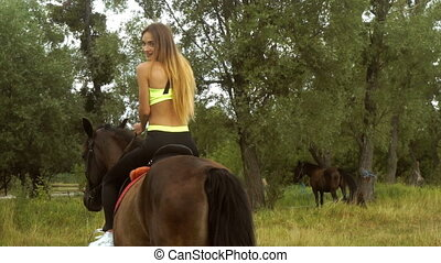 young beautiful lady rides a horse looks back
