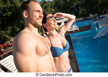 Upbeat couple looking into the distance at the resort