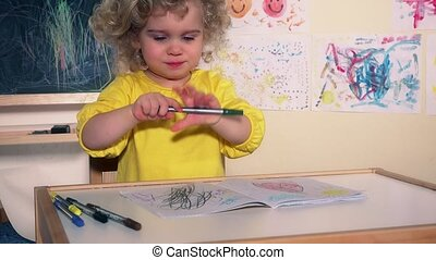 Funny artist child painting with pencil on paper sitting...