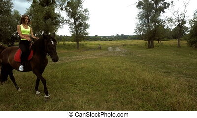 young cute girl rides on horseback in a circle on the nature