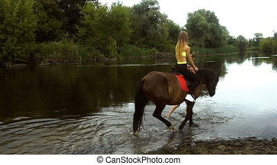 athletic girl riding her horse to water - a young athletic...