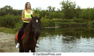 happy girl rides a horse on the Lake - happy young girl...