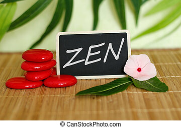 A slate with a zen  message next to red pebbles arranged in zen lifestyle on bamboo wood floor with a peony flower