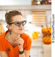 young woman in Halloween decorated kitchen looking aside