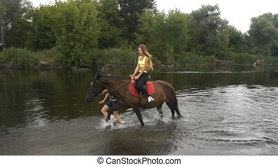 charming girl sitting on a horse and rides on the Lake -...