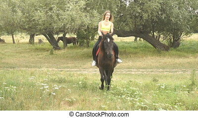 young cute girl rides on a horse on the grass on the street