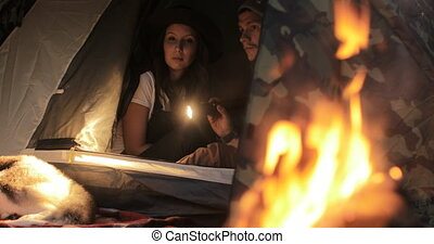 Couple in tent with flashlights near fire