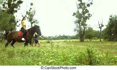 skinny girl jumps on a big brown horse on nature - young...