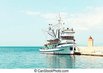 Fishing trawler at a pier next to a lighthouse - Fishing...