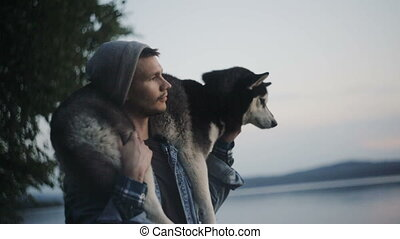Man is holding a dog on his shoulders - A man holds a Husky...