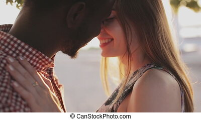 Caucasian and african couple kissing and looking into each...