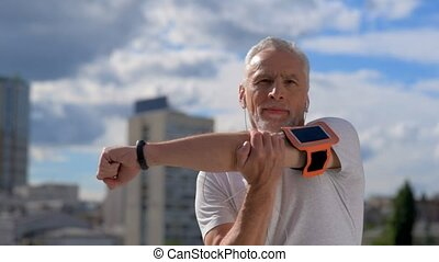 Confident senior man stratching his arms outdoors