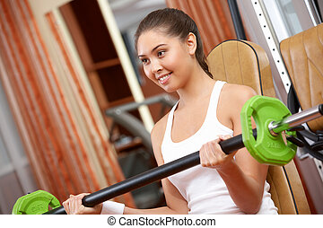 Weight lifting - Photo of active girl lifting dumbbell -...