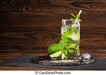Beautiful mojito cocktail with a straw, mint, ice cubes and slices of lime on the wooden background.  Copy space.