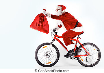 Santa with sack - Photo of happy Santa Claus on bike with...