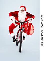 Santa on bicycle - Photo of happy Santa Claus with red sack...