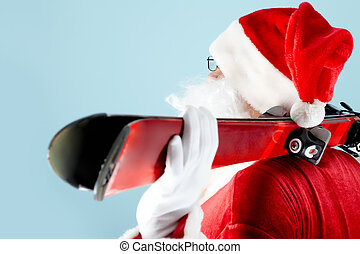 Santa with skis - Side view of Santa Claus with skis on blue...
