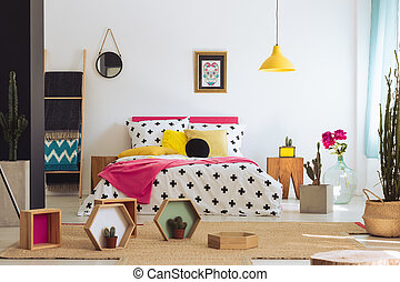 Geometric bedroom with colorful bed, cactus and cross duvet...