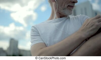 Positive aged man using his armband to choose right song -...