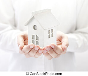Small white toy house in hands