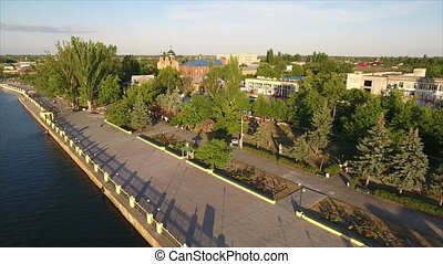 Aerial shot of the Dnipro river embankment with an asphalted road and greenary