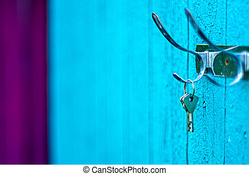 Keys hanging from a hook on the old painted wooden wall outside.  Ipmortant to keep your keys safe.