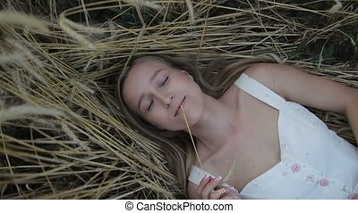 Dreamy girl lying on golden ripe wheat field - Beautiful...