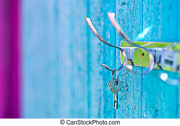 Keys hanging from a hook on the old painted wooden wall outside.  Important to keep your keys safe.