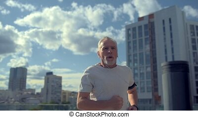 Cheerful senior man running in the urban surrounding -...
