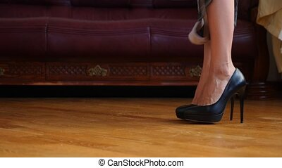 A sexy woman in black high-heeled shoes takes off her...